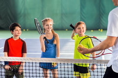 Allievi allegri che imparano giocar a tennise Immagine Stock Libera da Diritti