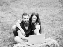 Allievi allegri ragazza o uomo barbuto felice e del donna che per mezzo del computer portatile sulla natura Fotografia Stock Libera da Diritti