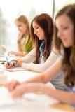 Allievi in aula che si siede in una riga Fotografia Stock