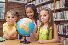 Allievi in biblioteca con il globo Fotografia Stock Libera da Diritti