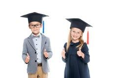 Allievi in cappelli di graduazione che mostrano i pollici su Fotografia Stock Libera da Diritti