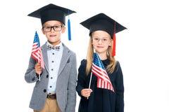 Allievi in cappelli di graduazione con le bandiere degli S.U.A. Immagini Stock Libere da Diritti