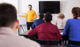 Allievi che ascoltano con le spiegazioni dei teacher's di interesse Immagini Stock