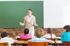 Allievi che ascoltano il loro insegnante alla lavagna Fotografia Stock