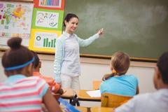 Allievi che ascoltano il loro insegnante alla lavagna Immagine Stock