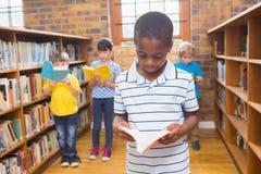 Allievi che cercano i libri in biblioteca Fotografia Stock