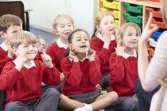 Allievi che copiano le azioni dell'insegnante mentre cantando canzone Fotografia Stock