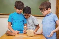Allievi che esaminano roccia con la lente d'ingrandimento Immagini Stock