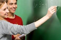 Allievi che fanno per la matematica sulla lavagna Immagine Stock