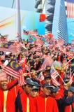 Allievi che fluttuano le bandierine della Malesia durante il giorno nazionale Immagini Stock Libere da Diritti