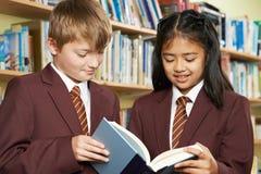 Allievi che indossano il libro di lettura dell'uniforme scolastico in biblioteca Fotografia Stock Libera da Diritti