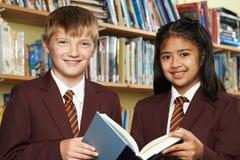 Allievi che indossano il libro di lettura dell'uniforme scolastico in biblioteca Immagini Stock
