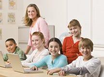 Allievi che lavorano ai computer portatili Fotografie Stock Libere da Diritti