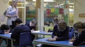 Allievi che lavorano alla Tabella con l'insegnante Helping Them video d archivio