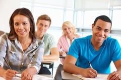 Allievi che lavorano nell'aula Immagine Stock