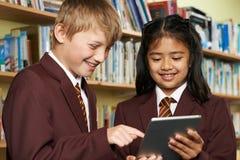 Allievi che portano uniforme scolastico facendo uso della compressa di Digital in biblioteca Fotografia Stock Libera da Diritti