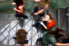 Allievi che scorrono veloce su e giù lle scala occupate Immagini Stock