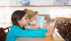Allievi che si siedono in libri di lettura dell'aula Fotografia Stock