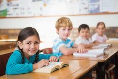 Allievi che si siedono in libri di lettura dell'aula Immagine Stock