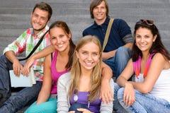 Allievi che si siedono sugli anni dell'adolescenza sorridenti delle scale del banco Fotografia Stock
