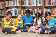 Allievi che si siedono sulla terra e sui libri di lettura nella biblioteca Fotografie Stock
