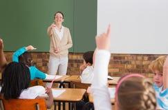 Allievi che sollevano le loro mani durante la classe Immagini Stock