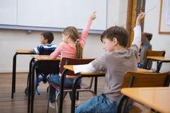 Allievi che sollevano le loro mani durante la classe Immagine Stock