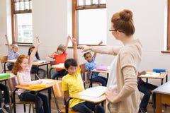 Allievi che sollevano le loro mani durante la classe Immagini Stock Libere da Diritti