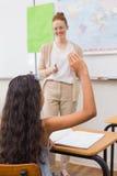 Allievi che sollevano mano durante la lezione di geografia in aula Fotografia Stock