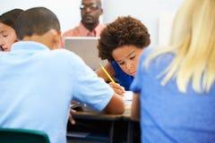 Allievi che studiano agli scrittori in aula Immagine Stock