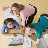 Allievi che utilizzano computer portatile nell'aula Immagini Stock