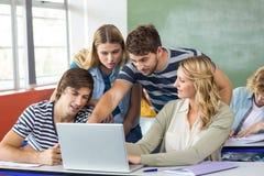 Allievi che utilizzano computer portatile nell'aula Immagine Stock Libera da Diritti