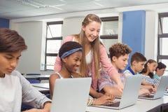 Allievi che utilizzano computer portatile nell'aula Fotografie Stock