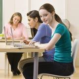 Allievi che utilizzano i computer portatili nell'aula Fotografie Stock