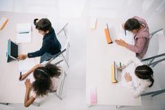 Allievi che utilizzano le compresse digitali mentre sedendosi agli scrittori nell'aula Fotografie Stock