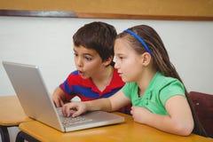 Allievi che utilizzano un computer portatile nella classe Immagine Stock Libera da Diritti