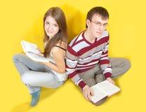 Allievi con i libri sopra un colore giallo Fotografia Stock