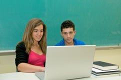 Allievi con il computer portatile in aula Fotografia Stock