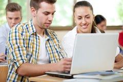 Allievi con il computer portatile in aula Fotografie Stock Libere da Diritti
