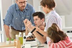Allievi con l'insegnante nella classe di chimica Immagini Stock