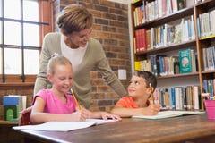 Allievi d'aiuto dell'insegnante in biblioteca Immagini Stock Libere da Diritti