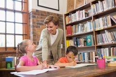 Allievi d'aiuto dell'insegnante in biblioteca Fotografia Stock