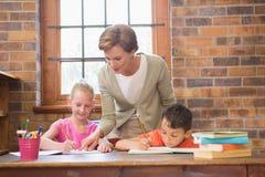Allievi d'aiuto dell'insegnante in biblioteca Fotografie Stock