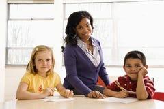 Allievi d'aiuto dell'insegnante con Schoolwork Immagini Stock Libere da Diritti