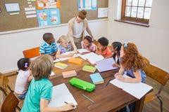 Allievi d'aiuto dell'insegnante grazioso in aula Fotografie Stock