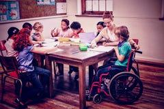 Allievi d'aiuto dell'insegnante grazioso in aula Fotografie Stock Libere da Diritti