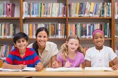 Allievi d'aiuto dell'insegnante grazioso in biblioteca Fotografia Stock Libera da Diritti