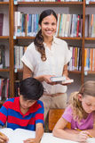 Allievi d'aiuto dell'insegnante grazioso in biblioteca Fotografie Stock Libere da Diritti