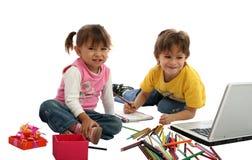 Allievi dei bambini con i pastelli ed il calcolatore. Fotografia Stock
