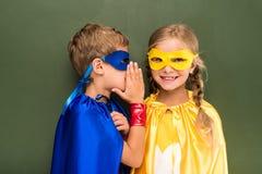 Allievi del fare chiacchiere in costumi del supereroe Fotografie Stock